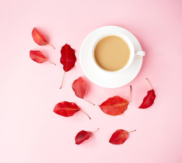 Fond plat d'automne sur rose. composition avec des feuilles rouges réalistes et une tasse de café. bonjour concept d'octobre