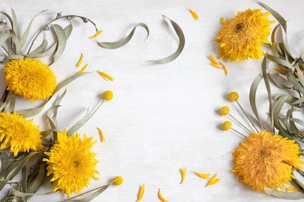 Fond plat blanc festif avec tournesols et fleurs de craspedia, espace de copie.