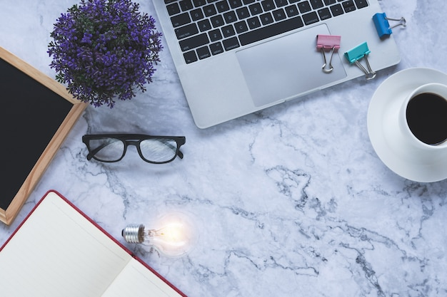 Fond plat créatif et designer avec des outils de bureau et ampoule