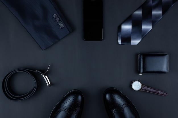 Fond plat laïque d'affaires avec un espace de copie. chaussures pour hommes, portefeuille de montre-bracelet, ceinture, téléphone portable et une cravate sur fond noir.