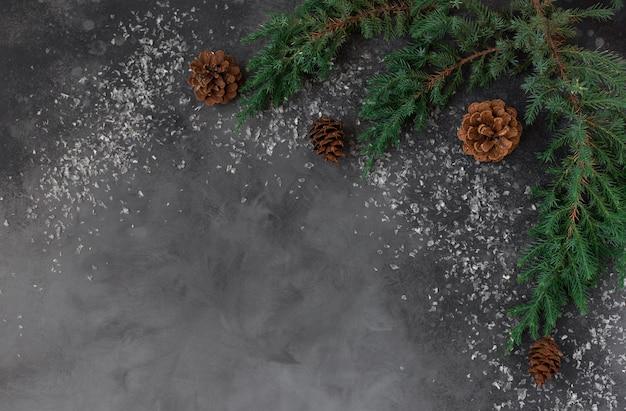 Fond plat de noël avec des décorations de branches de sapin, des cônes sur un fond sombre avec de la neige. copie espace