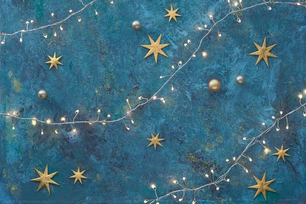 Fond plat de noël ou du nouvel an sur une planche texturée grunge sombre. vue de dessus, mise à plat avec des lumières sur une guirlande lumineuse de noël, des boules dorées et des étoiles brillantes. joyeux noël et bonne année!