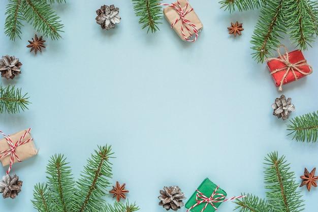 Fond plat de noël fait de branches de sapin, décorations, coffrets cadeaux et pommes de pin