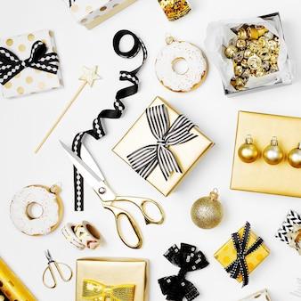 Fond plat de noël ou de fête avec des coffrets cadeaux, une bouteille de champagne, des arcs, des décorations et du papier d'emballage aux couleurs or et noir. mise à plat, vue de dessus