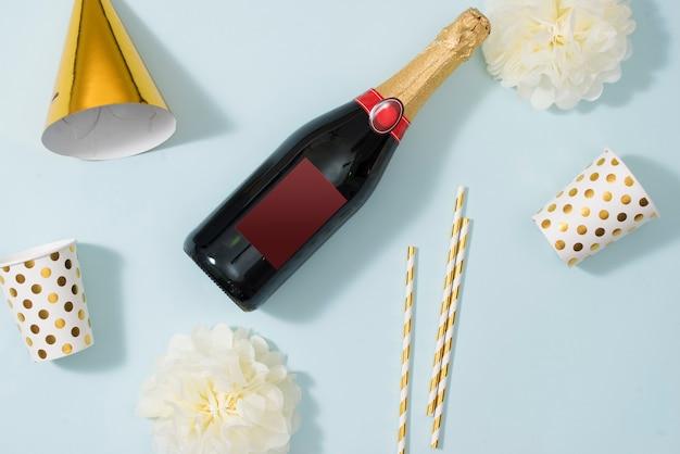 Fond plat de noël ou de fête avec des coffrets cadeaux, une bouteille de champagne, des arcs, des décorations et du papier d'emballage en or. mise à plat, vue de dessus