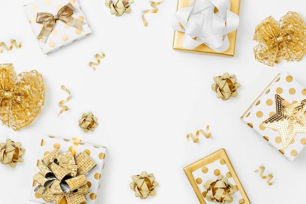 Fond plat de noël ou de fête avec des coffrets cadeaux et des décorations aux couleurs dorées. mise à plat, vue de dessus