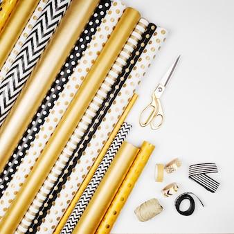 Fond plat de noël ou de fête avec des coffrets cadeaux, des rubans, un arc, des décorations et du papier d'emballage aux couleurs or et noir. mise à plat, vue de dessus