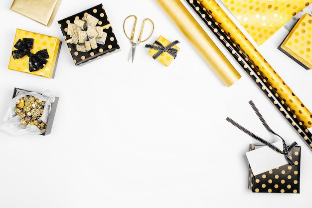 Fond plat de noël ou de fête avec des coffrets cadeaux, des rubans, des décorations et du papier d'emballage aux couleurs or et noir. mise à plat, vue de dessus