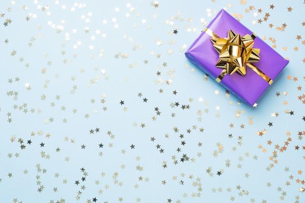 Fond plat pour la célébration de noël et du nouvel an. les coffrets cadeaux sont violets avec des nœuds de rubans dorés et des étoiles de confettis sur fond bleu. vue de dessus copie espace.