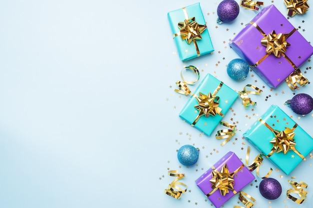 Fond plat pour la célébration de noël et du nouvel an. les coffrets cadeaux sont violets et turquoises avec des nœuds de rubans dorés et des étoiles de confettis sur fond bleu. vue de dessus copie espace.