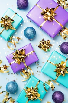 Fond plat pour la célébration de noël et du nouvel an. les coffrets cadeaux sont violets et turquoises avec des nœuds de rubans dorés et des étoiles de confettis sur fond bleu. vue de dessus