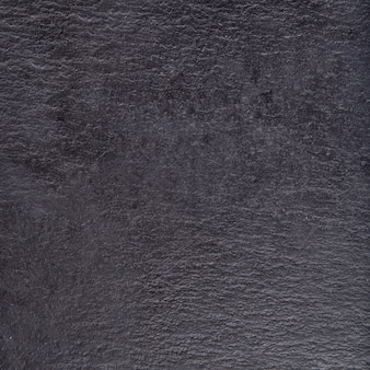 Fond de plateau en pierre de basalte au fromage, support à fromage, plateau en ardoise. ardoise de pierre noire, gros plan.