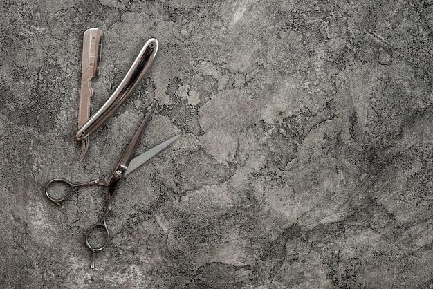Sur un fond de plâtre gris, se trouvent un rasoir et des ciseaux.