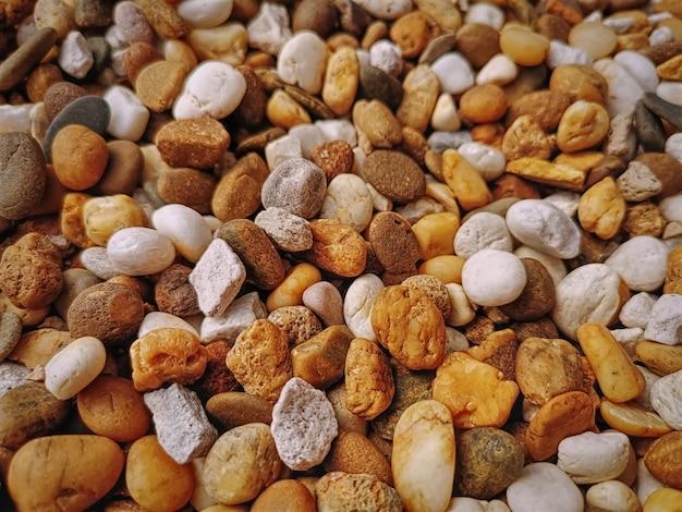 Fond plein cadre de petites pierres de galets brunes et blanches