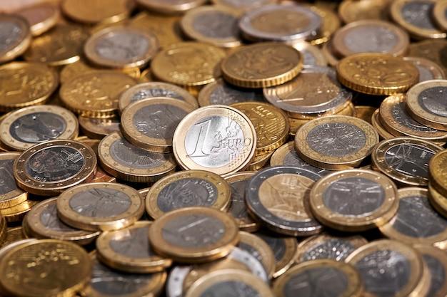 Fond plein cadre d'une pièce de 1 euro placée sur une pile de pièces brillantes