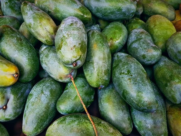 Fond plein cadre de tas de mangues mûres vertes fraîches au marché