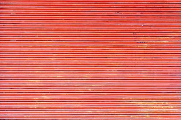 Fond de porte de volet roulant en acier de couleur rouge.
