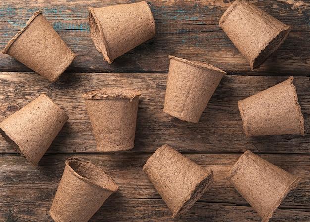 Fond avec des pots de tourbe disposés au hasard sur une table en bois. vue de dessus. le concept de culture.