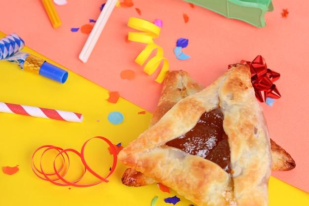 Fond de pourim avec des costumes de fête et des biscuits hamantaschen.