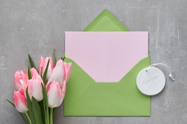 Fond de printemps avec une carte-cadeau vide dans une enveloppe verte