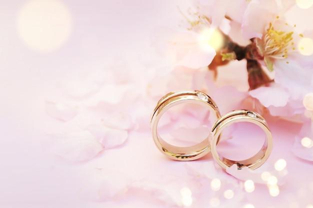 Fond de printemps avec fleur et anneaux de mariage