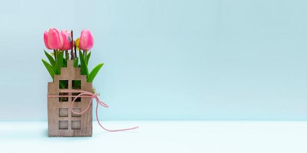 Fond de printemps avec tulipe rose et chat dans un récipient en bois vintage.