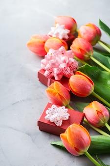 Fond de printemps avec des tulipes colorées oranges et boîte-cadeau, femmes, fête des mères, carte de voeux, image de l'espace de copie