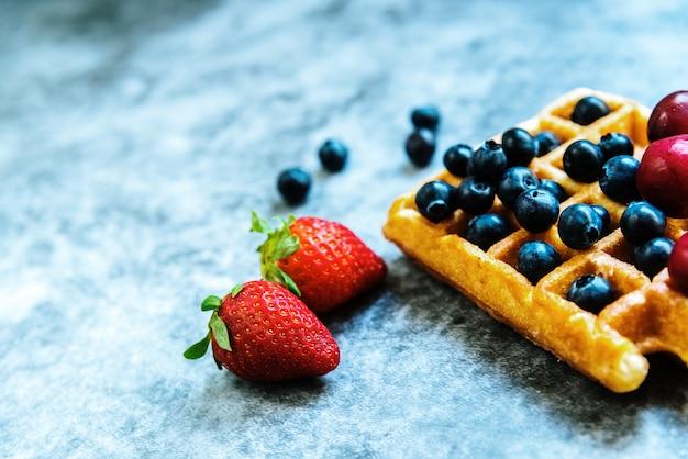 Fond propre avec espace négatif pour des aliments sains et des fruits antioxydants, et une gaufre comme malbouffe.