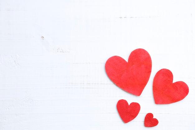 Fond de quatre coeurs en bois sur une vieille table blanche rustique