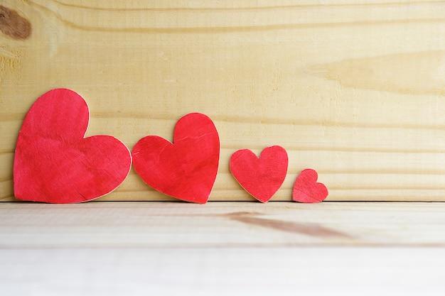 Fond de quatre coeurs en bois sur une vieille table rustique