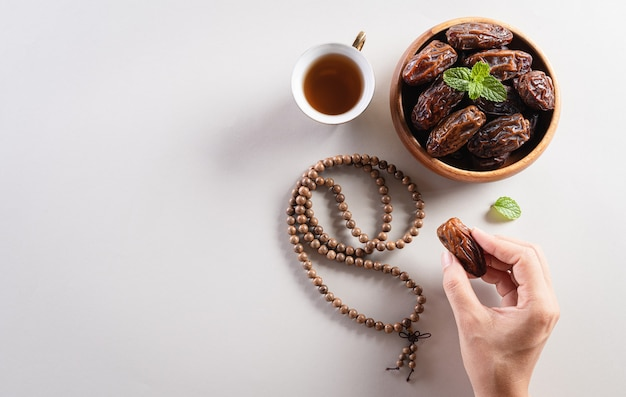 Fond de ramadan kareem, mains ramassant des fruits, du thé et des perles de chapelet.
