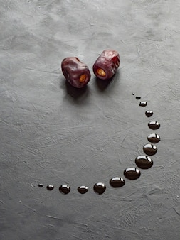 Fond de ramadan noir avec des dates et du sirop de dattes versées en forme de croissant de lune.