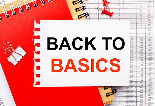 Sur le fond des rapports, il y a des blocs-notes rouges et marrons, un trombone blanc, des boutons rouges et une feuille de papier blanche avec le texte retour aux bases. concept d'entreprise