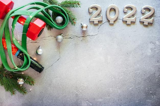 Fond de remise en forme du nouvel an avec haltères, bande de résistance, branches d'arbres de noël et numéros 2022