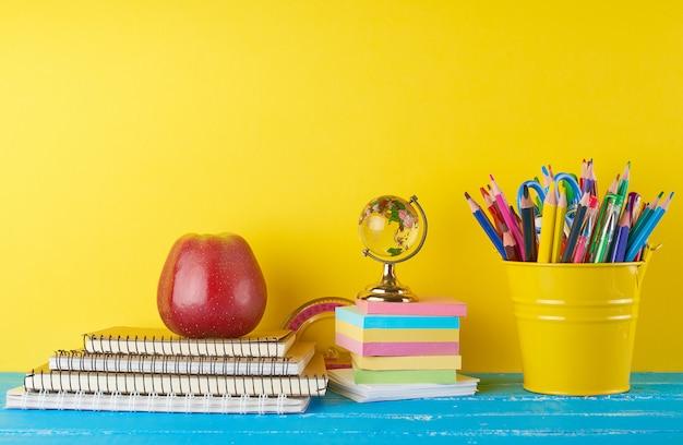 Fond de retour à l'école avec des crayons, des blocs-notes et des pommes pour enfants