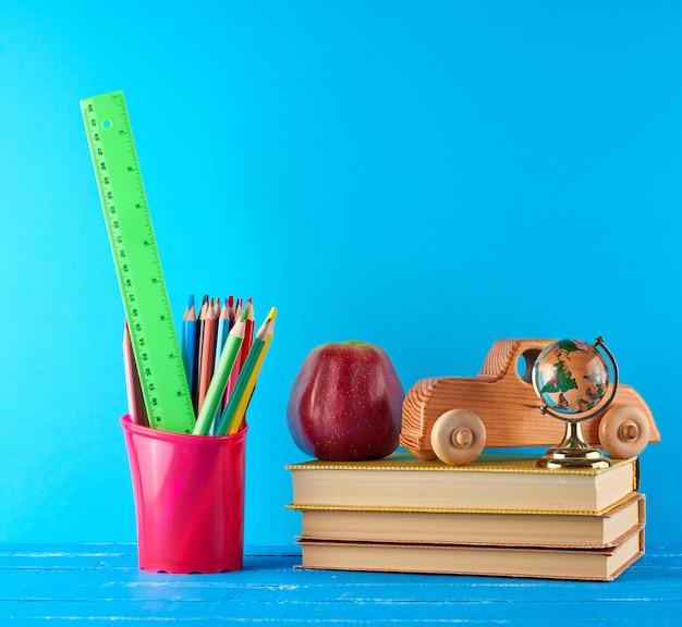Fond de retour à l'école avec des crayons de papeterie pour enfants, des livres, des pommes