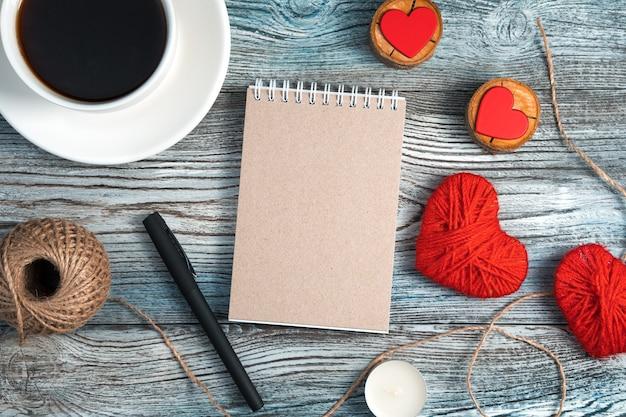 Fond romantique avec bloc-notes, tasse à café et coeurs sur fond en bois.