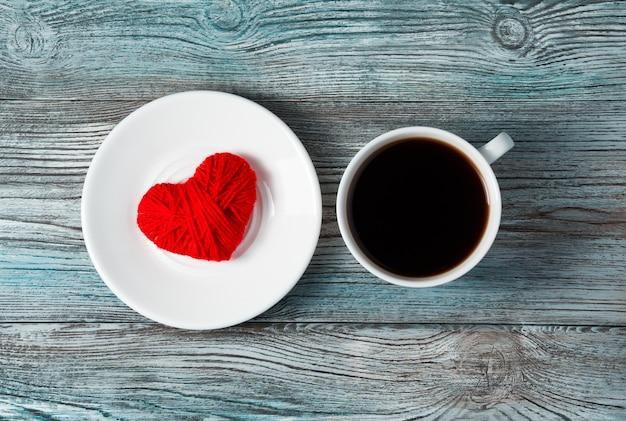 Fond romantique avec coeur rouge, soucoupe et tasse à café sur fond en bois gris-bleu.