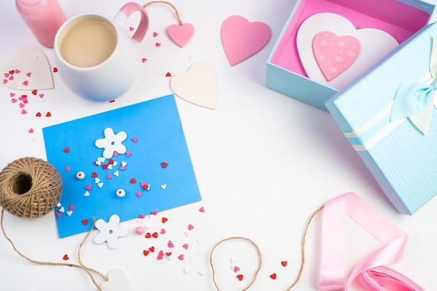 Fond romantique avec coeurs, enveloppe, boîte-cadeau et tasse à café en fleurs roses sur une lumière