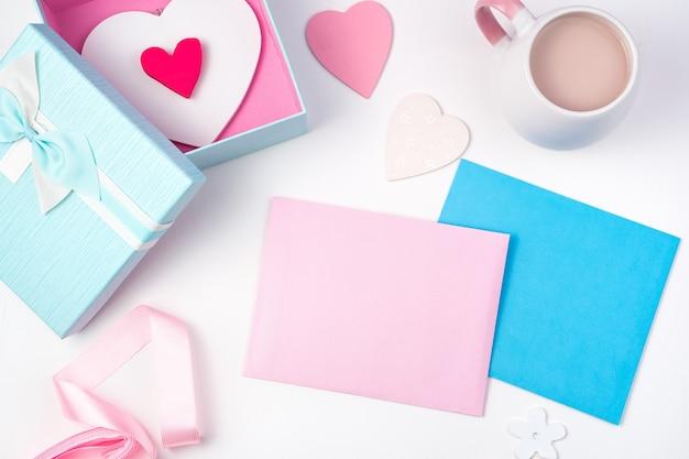Fond romantique avec deux enveloppes, une boîte-cadeau avec des coeurs, une tasse de café et des rubans sur un