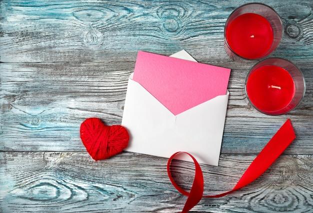 Fond romantique avec enveloppe, coeur, bougies et ruban sur un fond gris-bleu en bois.