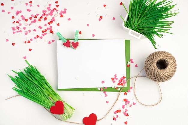 Fond romantique avec des enveloppes, un bouquet d'herbe de blé et de coeurs sur fond clair.