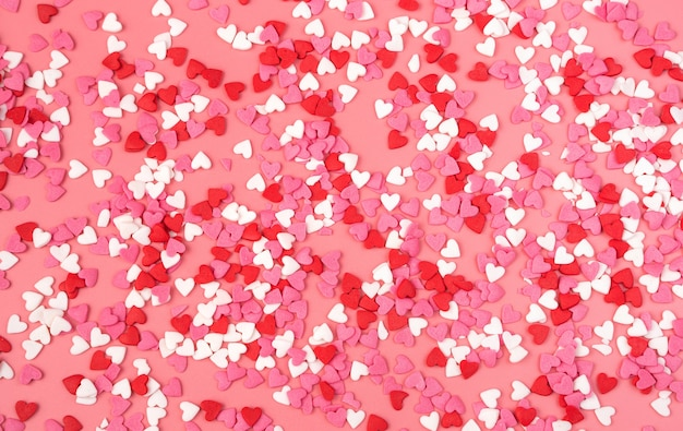 Fond romantique avec petits coeurs sur fond rose. la vue du haut. concept 14 février.