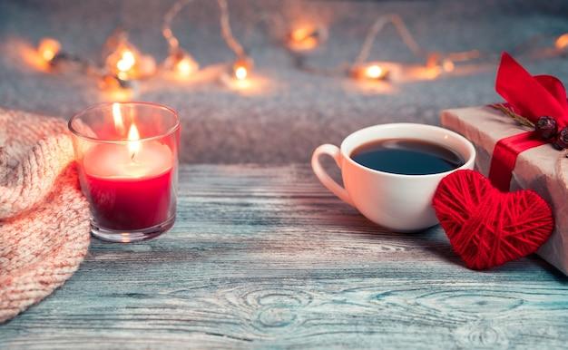 Fond romantique avec tasse à café, cadeau, coeur et espace de copie.