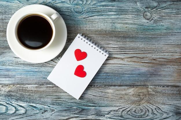 Fond romantique avec une tasse de café et deux coeurs sur un bloc-notes sur un gris-bleu en bois
