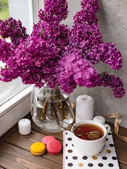 Fond romantique avec tasse de thé, fleurs lilas et macarons.