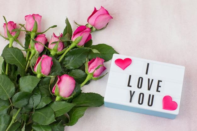 Sur fond rose un bouquet de roses roses et l'inscription je t'aime
