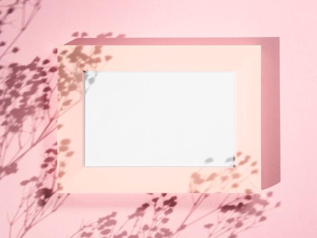 Fond rose avec un cadre photo rose et des ombres de branche