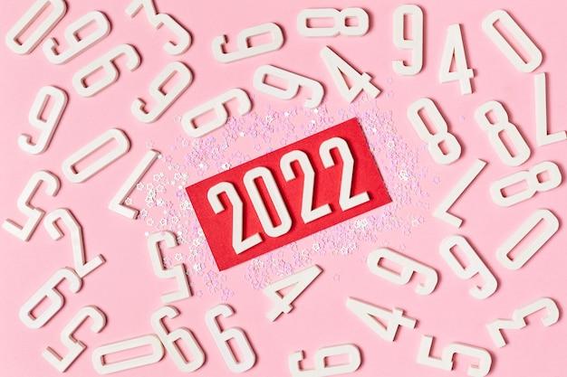 Fond rose de chiffres avec lettrage au centre 2022, décoré d'étincelles de noël