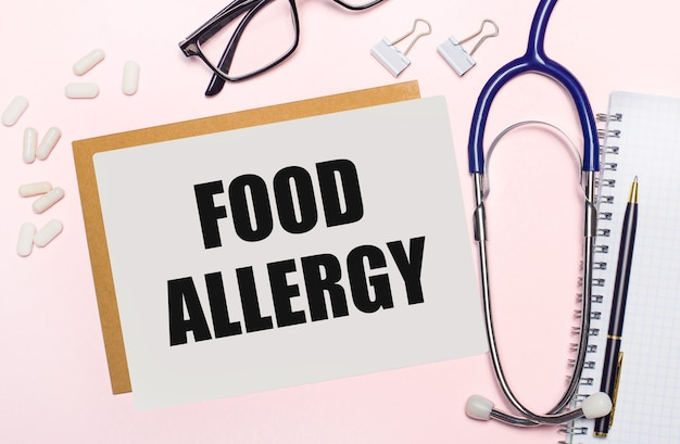 Sur un fond rose clair, un cahier avec un stylo, un stéthoscope, des pilules blanches, des trombones et une feuille de papier avec le texte food allergy. notion médicale